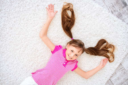 Joyful smiling child girl lying on a floor and having a rest at home. Happy childhood.