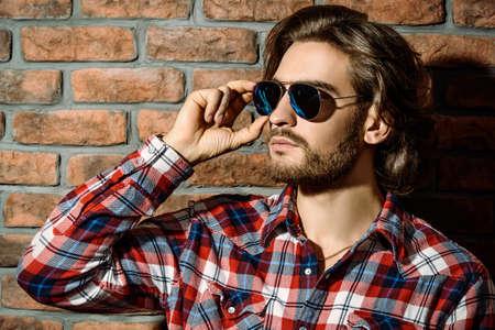 잘 생긴 젊은 남자 벽돌 벽에 서 선글라스. 남자의 아름다움, 패션. 남성 이발소, 헤어 스타일.