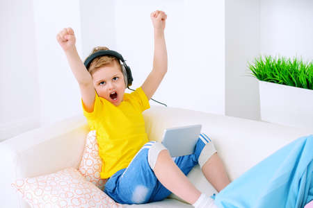 Joyful excited boy listening to music in headphones at home. Happy childhood. Activity for children. Stock Photo