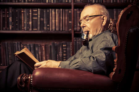 An old intelligent man reading a book in his library at home. Retirement. Retro style.