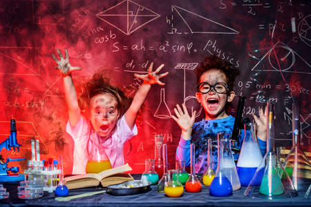 Funny little children doing experiments in the laboratory. Explosion in the laboratory. Science and education. Archivio Fotografico