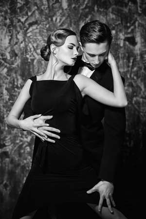 Black-and-white portrait of a beautiful passionate dancers dancing tango. Couple in love dancing on a date. Love concept.