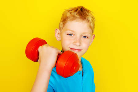 Portrait of a boy with dumbbells over yellow background. Healthy lifestyle. Sports and activities for children.