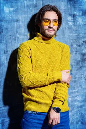 노란색 풀 오버와 선글라스를 착용 잘 생긴 남자입니다. 남자의 아름다움, 패션. 남성용 헤어 스타일. 스톡 콘텐츠