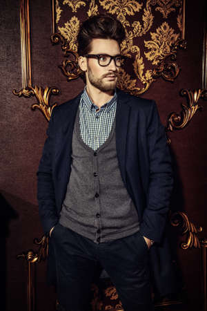 Portrait of a well-dressed imposing man in elegant glasses posing in apartments with luxurious classic interior. Mens beauty, fashion. Hair styling, barbershop. Stock Photo