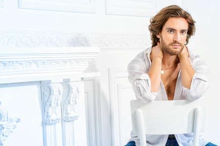 흰색 셔츠 카메라를 찾고 입고 잘 생긴 섹시한 남자. 남성 뷰티, 패션 모델. 헤어 스타일링.