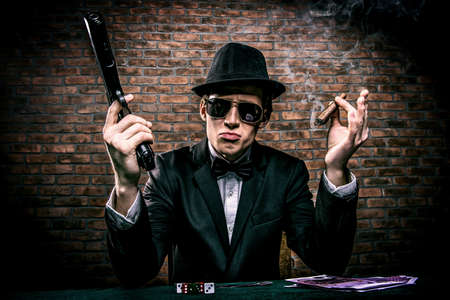 Cool gangster with a bunch of money threatens gun. Gambling industry, casino. Underworld concept.