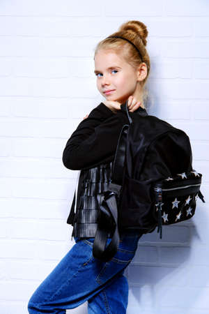 Childrens fashion. Modern eight year old girl posing in casual jeans and leather jacket and backpack. Studio shot. Education. Stock Photo