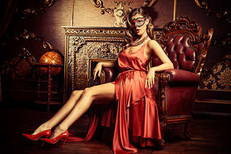 Charming elegant woman in beautiful red dress and masquerade mask is sitting in a chair in a luxury apartment. Classic vintage interior. Beauty, fashion. Retro style.