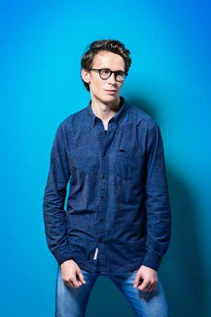 밝은 파란색 배경 위에 포즈 캐주얼 청바지 옷과 안경 젊은 남자. 남성 뷰티, 패션. 광학 스타일. 스톡 콘텐츠