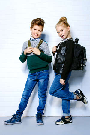 Children's fashion. Modern boy and girl posing together at studio. Education. 스톡 콘텐츠