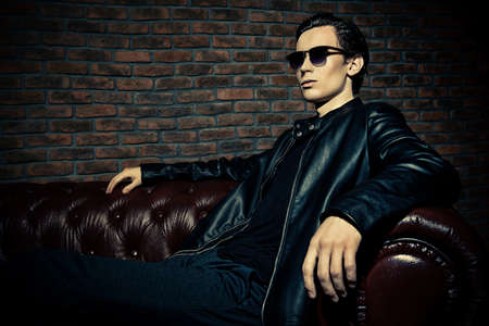 Portrait of a handsome confident young man sitting relaxed on a couch. Mens beauty, fashion. Stock Photo