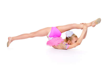 Beautiful little gymnast girl doing gymnastics. Professional sports. Isolated over white. Copy space.