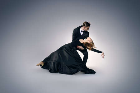 Couple of professional dancers performing tango. Beautiful young people in love dancing on a date. Studio shot. Фото со стока