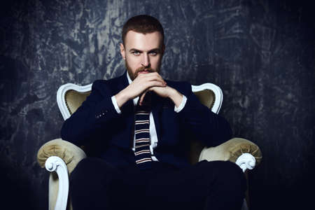 Respectable handsome man sitting in classical vintage armchair. Mens beauty, fashion. Luxurious lifestyle.