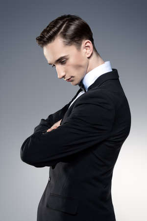 Portrait of a handsome young man in elegant black suit and a bow-tie. Male beauty, fashion. Studio shot.