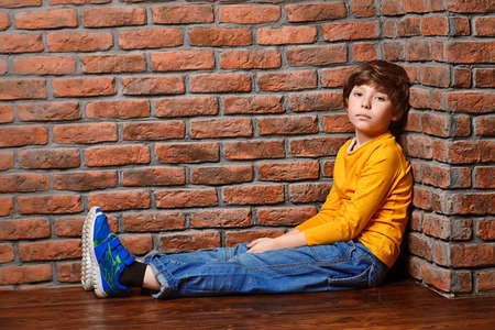 Portrait of a cute nine year old boy sitting on a floor leaning against the brick wall. Clothes for children. Kids fashion.