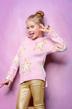 Portret van een gelukkig lachende meisje over roze achtergrond. Stockfoto