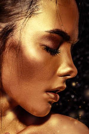Beauty-Konzept. Close-up-Porträt einer schönen jungen Frau mit leuchtender goldener Haut. Hautpflege-Produkte, Kosmetik. Schmuck-Konzept. Standard-Bild - 76059035