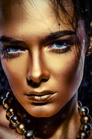 아름다움 개념입니다. 빛나는 황금 피부와 아름 다운 젊은 여자의 클로즈 업 초상화. 스킨 케어 제품, 화장품. 보석 개념입니다. 스톡 콘텐츠