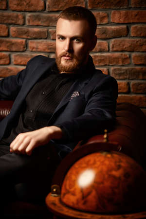 Imposing well dressed man sitting on a Chesterfield leather couch. Mens beauty, fashion.