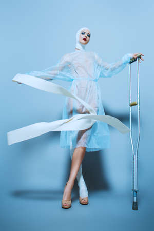 Fashion shot. Gorgeous female model in bandages and hospital gown posing at studio with crutches. Beauty and medicine, plastic surgery. Imagens