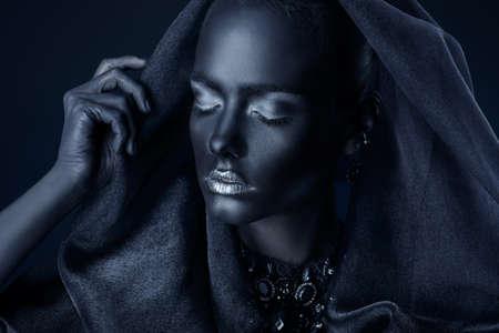 完璧な黒肌と美しいネックレス、黒いベールを身に着けているシルバーのキラキラ唇を持つ美しい若い女性。化粧品とメイクアップ。宝石や宝石で