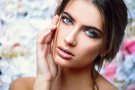 Mooie sensuele vrouw stellen op een achtergrond van rozen. Inspiratie van de lente en de zomer. Parfum, cosmetica concept.