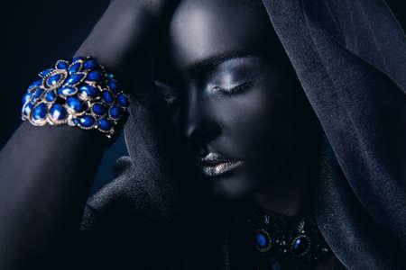 Belle jeune femme avec une peau noire parfaite portant un beau bracelet avec des pierres précieuses et un voile noir. Bijoux et bijouterie. Projet de peinture corporelle. Style africain. Banque d'images - 76248559