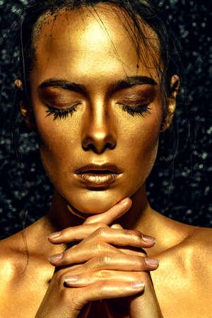 Beauty-Konzept. Close-up-Porträt einer schönen jungen Frau mit leuchtender goldener Haut. Hautpflege-Produkte, Kosmetik. Schmuck-Konzept. Standard-Bild - 76655404