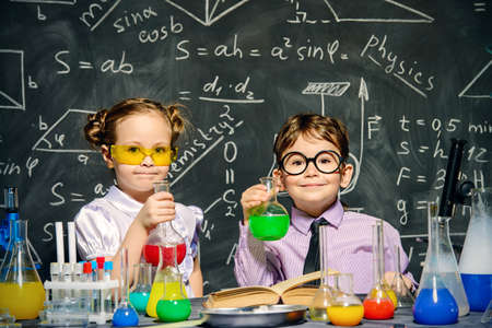 Two little children scientists making experiments in the laboratory.