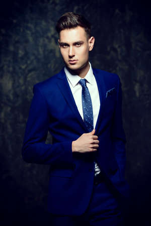 Fashion shot of a handsome young man in elegant classic suit.