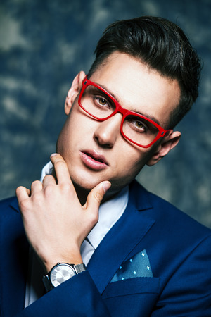 Fashion shot of a handsome young man in elegant classic suit and spectacles. Stock Photo