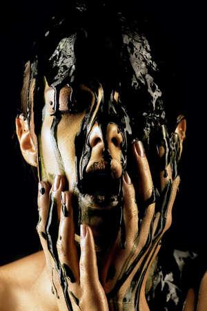 Porträt einer jungen Frau mit goldener Haut und schwarzem Öl , der auf ihr gießt Standard-Bild - 76685545