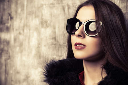 Attractive young woman wearing black sunglasses and fur coat. Studio shot. Beauty, fashion concept.