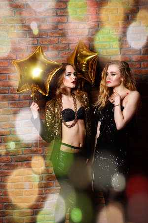 Two glamorous sexy girls at a night party. Beauty, fashion. Entertainment.