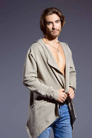 Handsome young man wearing hooded jacket and revealing his chest. Male beauty, fashion. Studio shot.