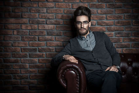 Imposing handsome man in elegant formal clothes and glasses. Fashion hair styling, barbershop. Brick wall background. Business style. Stock Photo