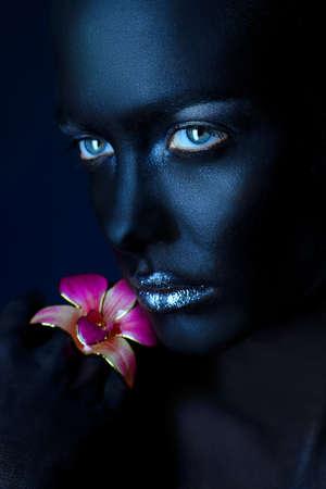 Beauty Portrait. Close-up-Porträt einer schönen jungen Frau mit perfekter schwarzer Haut mit Orchidee Brosche aufwirft. Body Painting Projekt. Kosmetik und Make-up. Schmuck. Standard-Bild - 76865486