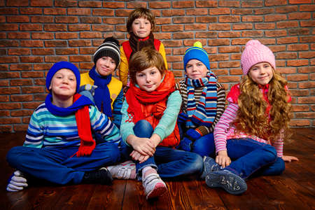 Group of happy joyful children posing together at studio by the brick wall. Kids fashion. Winter clothes.