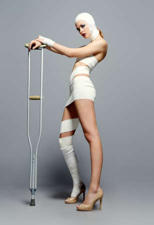 Mode erschossen. Herrliches weibliches Modell in den Verbänden und in Krankenhauskleid, die am Studio mit Krücken aufwerfen. Schönheit und Medizin, plastische Chirurgie. Standard-Bild - 77053543