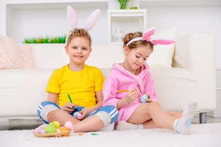 Easter holidays. Happy children painting eggs for Easter at home.