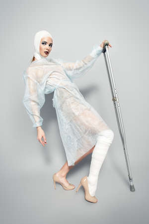 Fashion shot. Gorgeous female model in bandages and hospital gown posing at studio with crutches. Beauty and medicine, plastic surgery. Stock Photo