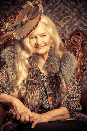 Fashionable old woman with beautiful blonde hair and elegant hat posing in vintage interior.