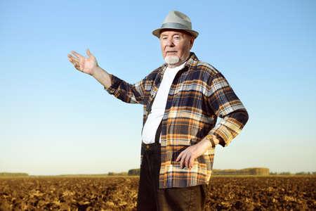 보았다고 필드에 서있는 노인 농부. 스톡 콘텐츠 - 77606496