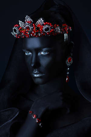 Jewelry industry. Fashion portrait of a beautiful young woman with perfect black skin wearing diadem with precious stones and black veil. Jewelry and bijouterie. Body painting project. Stock Photo