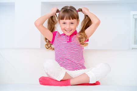 Freudig lächelnd Kind Mädchen sitzt auf einem Sofa und eine Pause zu Hause. Glückliche Kindheit. Standard-Bild