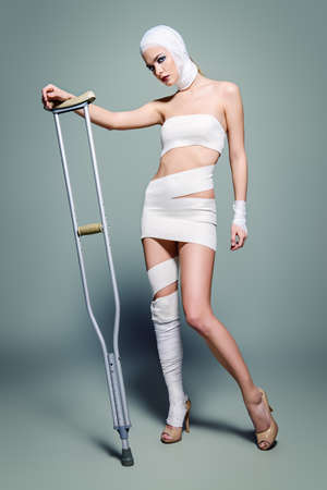Fashion shot. Gorgeous female model in bandages posing at studio with crutches. Beauty and medicine, plastic surgery. Stock Photo
