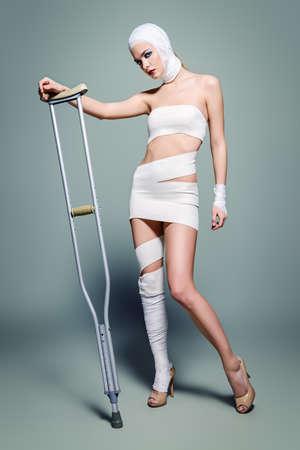Mode schot. Schitterend vrouwelijk model in verbanden die bij studio met steunpilaren stellen. Schoonheid en medicijnen, plastische chirurgie.