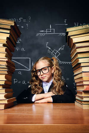 Portrait of a smart schoolgirl in glasses posing with books over school blackboard. Educational concept. Reklamní fotografie